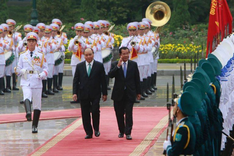 Cambodian Prime Minister Hun Sen, center right, and his Vietnamese counterpart Nguyen Xuan Phuc, center left, review an honor guard in Hanoi, Vietnam Friday Dec. 7, 2018. TRAN VAN MINH/AP